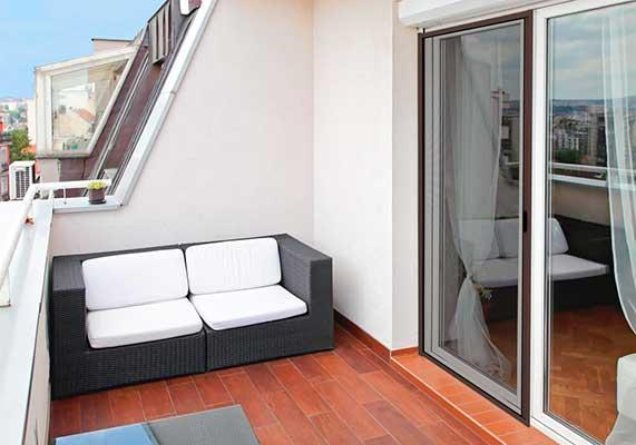 Terraza con mosquitera en la puerta para evitar que los gatos accedan a ella y sufran caídas